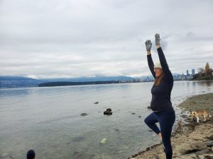 Diana Mello practices her tree pose at the beach.